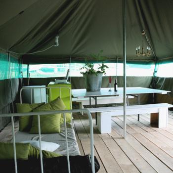 Два десятка брутальных «африканских» палаток установлены в вязовом лесу.