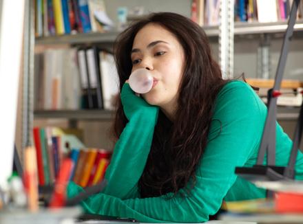 Девушка надувает пузырь из жвачки