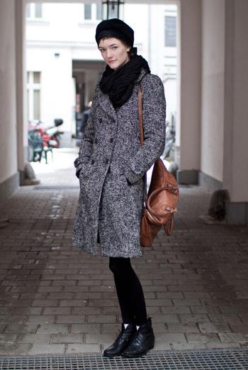 Девушка по имени Martina из Берлина сочетает серое двубортное пальто с аккуратными ботинками без каблуков и коричневой сумкой на длинной ручке.