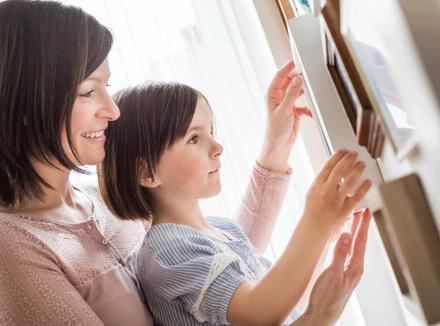 Мать и дочь вешают фото на стену