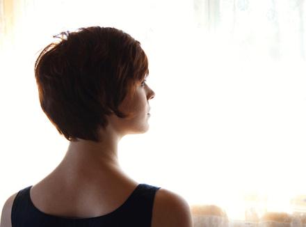 Решительная женщина на фоне окна