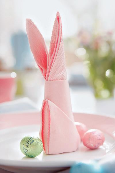 Не забудьте про салфетки. Их можно сложить в виде вот такого стилизованного пасхального зайца (см. схему). Яйца могут быть и шоколадными, например, как эти, завернутые в золотую фольгу.