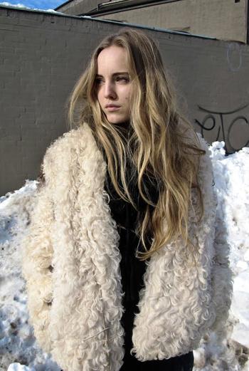 Широкие короткие шубки носят как в Лондоне, так и в Копенгагене. Крупный кудрявый ворс верхней одежды подчеркивает красоту юной девушки с волосами цвета льна.
