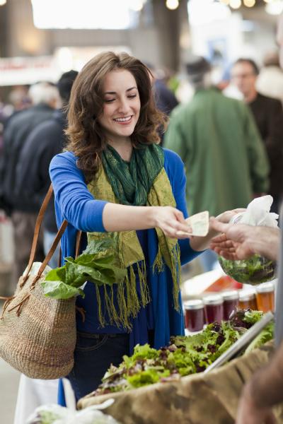 Женщина покупает овощи на рынке фото