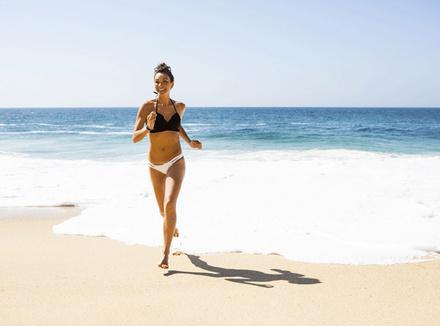 Женщина, бегущая по пляжу