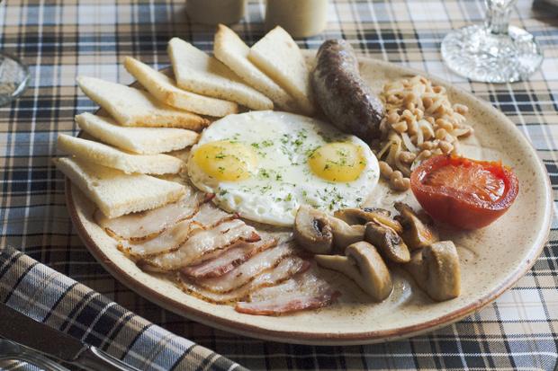 Яичница с жареными колбасками, беконом, горячим тостом
