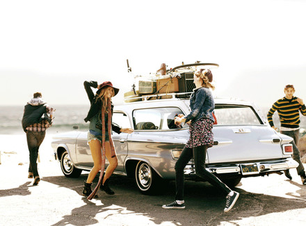 Группа молодых бегает вокруг машины