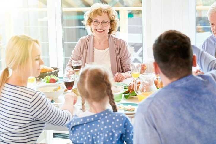 Большая семья ужинает за столом