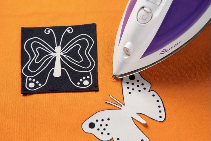 Используя «паутинку», на лицевой стороне оранжевого полотна фиксируют тканевую аппликацию.